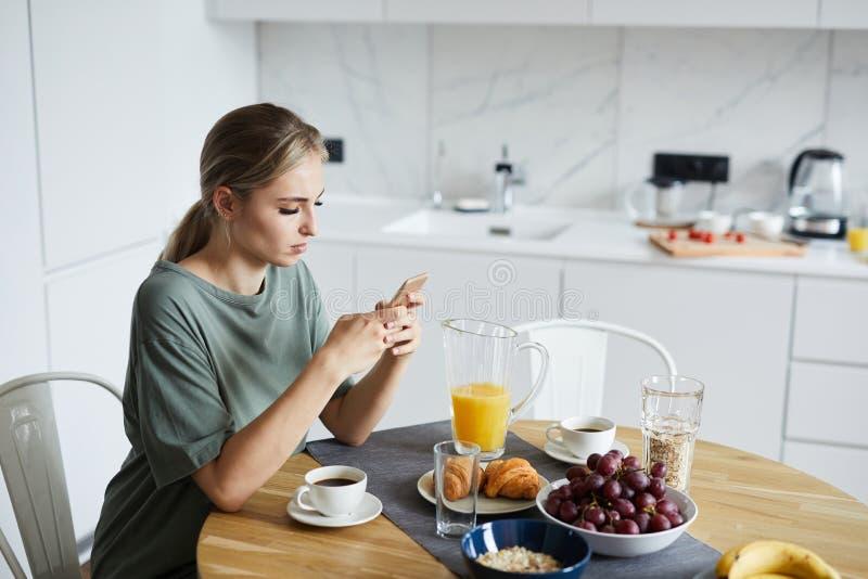 Jonge aantrekkelijke vrouw die smartphone gebruiken terwijl het hebben van ontbijt royalty-vrije stock fotografie