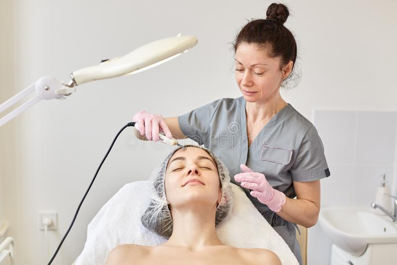 Jonge aantrekkelijke vrouw die ultrasone gezichtshuid het reinigen behandeling krijgt door professionele cosmetologist, in schoon stock fotografie