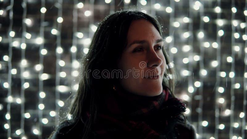 Jonge aantrekkelijke vrouw die van dalende sneeuw genieten bij Kerstnacht voor het decoratieve muurhoogtepunt van het fonkelen li royalty-vrije stock afbeelding