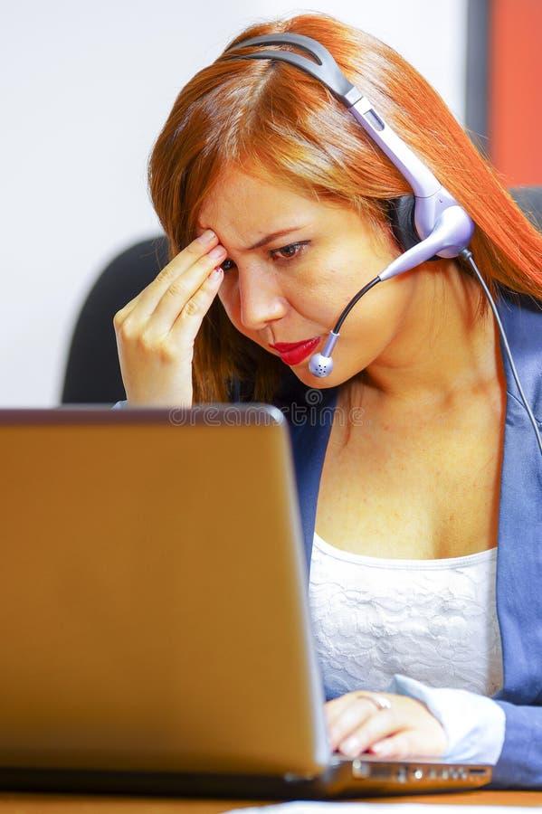 Jonge aantrekkelijke vrouw die van de bureaukleren en hoofdtelefoon zitting dragen door bureau die het computerscherm bekijken, d royalty-vrije stock foto