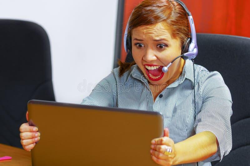 Jonge aantrekkelijke vrouw die van de bureaukleren en hoofdtelefoon zitting dragen door bureau die het computerscherm bekijken, h royalty-vrije stock foto