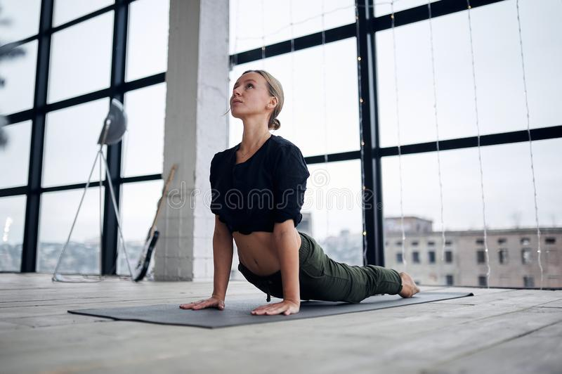 Jonge, aantrekkelijke vrouw die yoga in de loft studio oefent royalty-vrije stock foto
