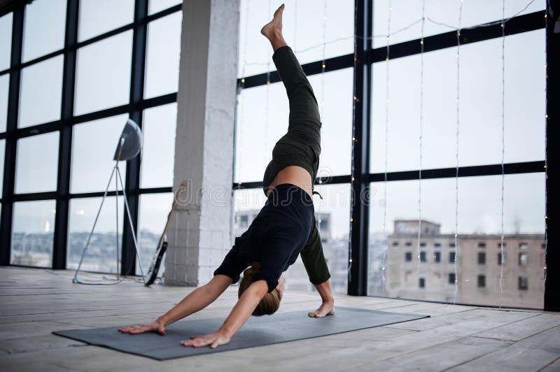 Jonge, aantrekkelijke vrouw die yoga in de loft studio oefent royalty-vrije stock foto's