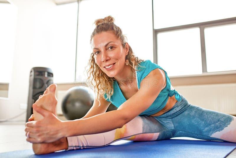 Jonge aantrekkelijke vrouw die yoga in geschiktheidsruimte doen Natuurlijke lichte omringend stock foto's