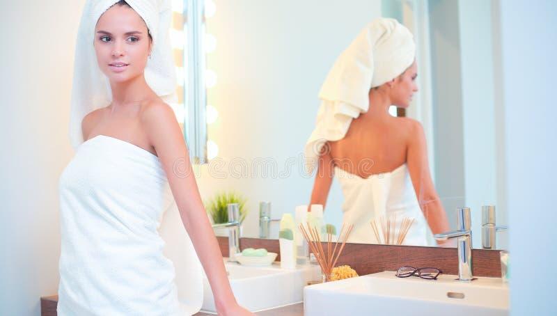 Download Jonge Aantrekkelijke Vrouw Die Zich Voor Badkamersspiegel Bevinden Stock Afbeelding - Afbeelding bestaande uit haar, zorg: 107704921