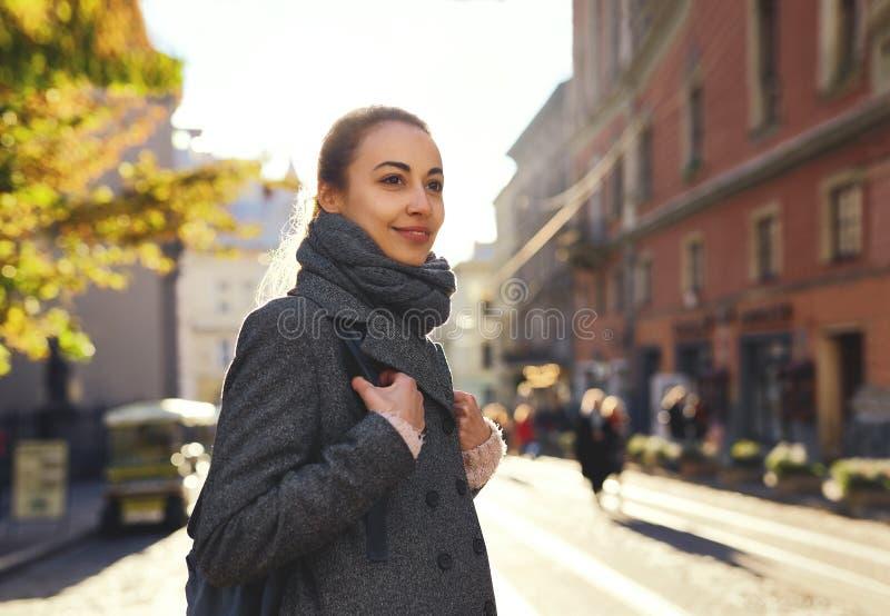 Jonge aantrekkelijke vrouw in een warme sjaal en een grijze laag het lopen stadsstraat royalty-vrije stock foto