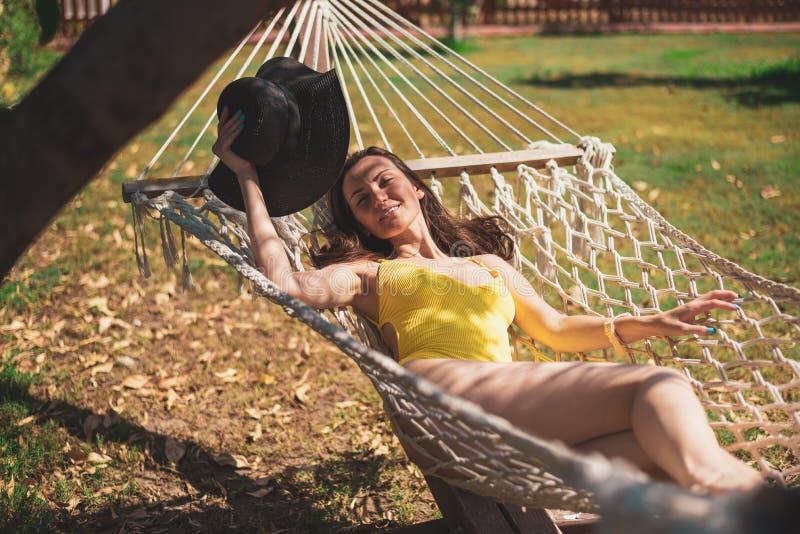 Jonge aantrekkelijke vrouw in geel zwempak die in een hangmat onder een boom rusten stock foto