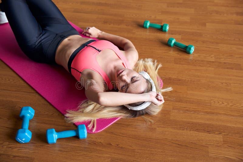 Jonge aantrekkelijke vrouw in gymnastiekkleren en hoofdtelefoons die na een training op de sportenmat rusten naast de domoren stock afbeeldingen