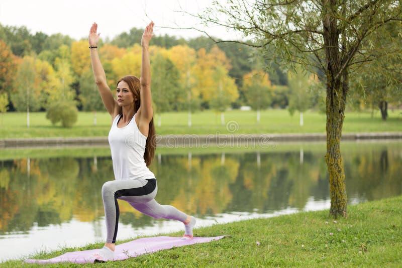 Jonge aantrekkelijke vrouw het praktizeren yoga, die zich in Strijder één oefening, Virabhadrasana bevinden die ik, het uitwerken royalty-vrije stock foto's