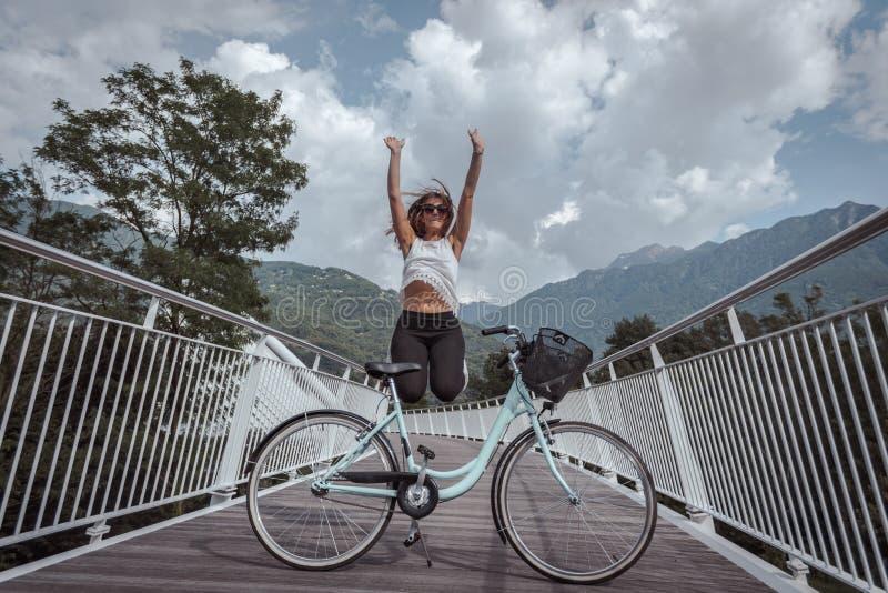 Jonge aantrekkelijke vrouw met fiets op een brug stock afbeeldingen