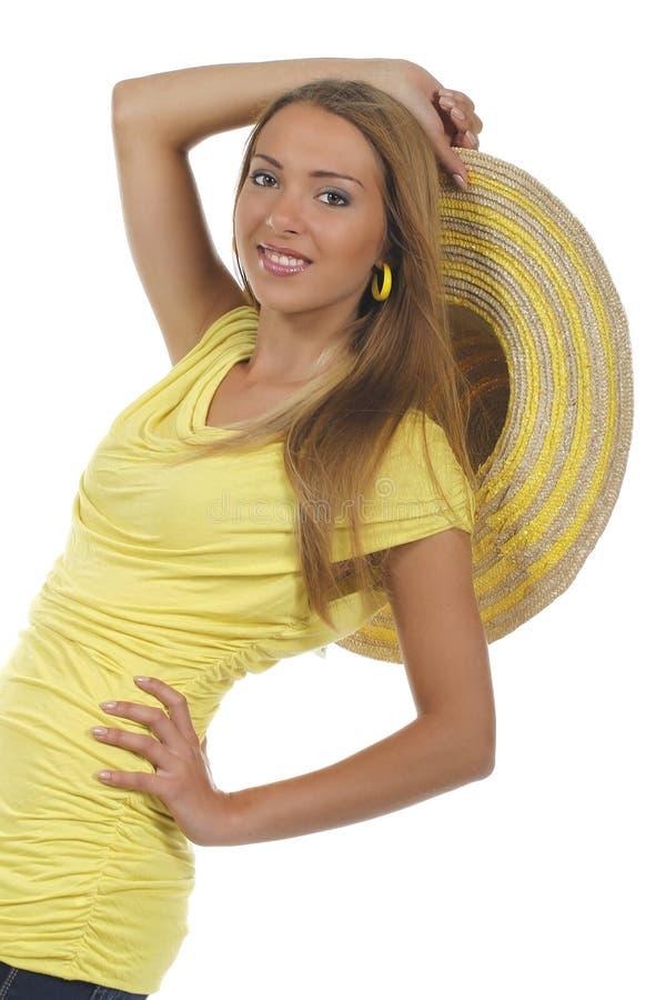 Jonge aantrekkelijke vrouw met geel overhemd en strawhat stock afbeelding