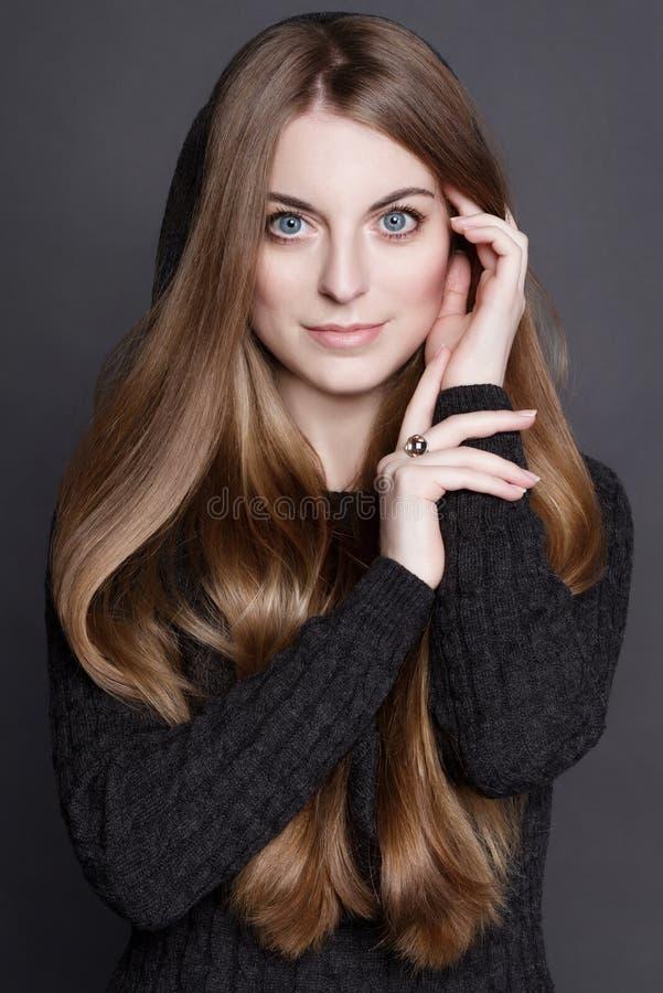 Jonge aantrekkelijke vrouw met lang, schitterend donker blond haar en grote blauwe ogen stock foto