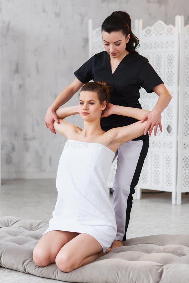 Jonge aantrekkelijke vrouw op behandelingsprocedure terwijl vrouwelijke therapeut streching handen van patint Dolly schot royalty-vrije stock foto