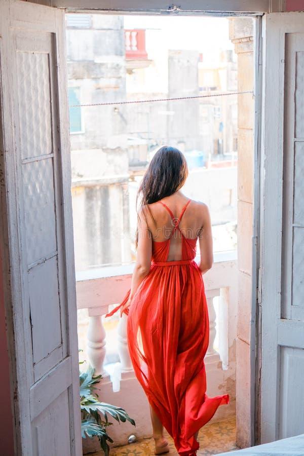 Jonge aantrekkelijke vrouw in rode kleding op oud balkon in flat in Havana stock afbeeldingen