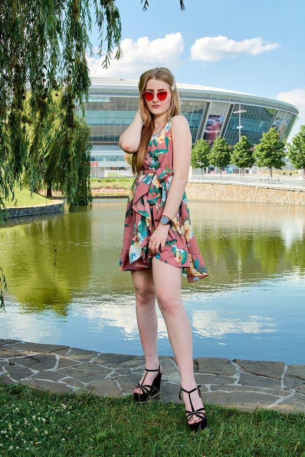 Jonge aantrekkelijke vrouw Rode zonnebril, kleurenkleding Meisjes` s portret De achtergrond van het voetbalstadion royalty-vrije stock fotografie