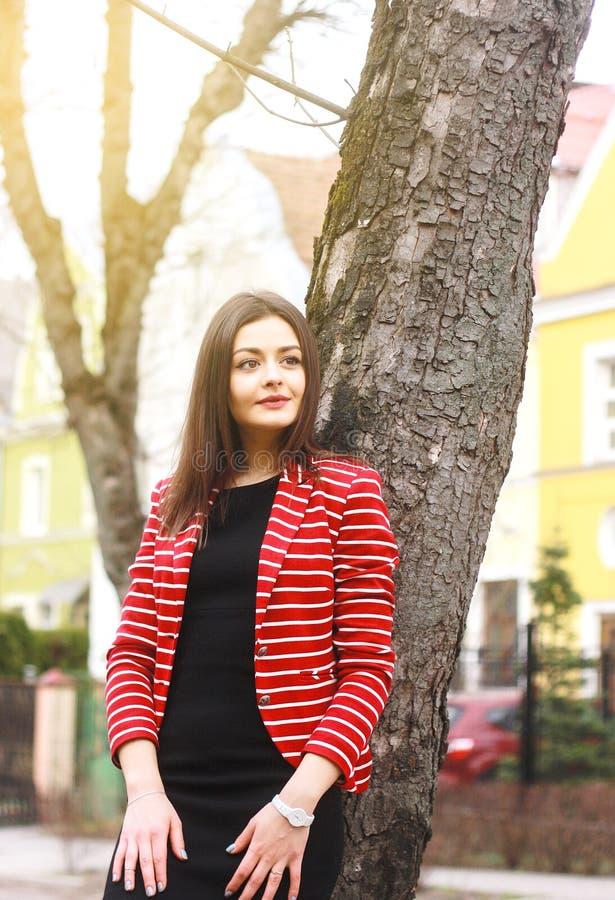 Jonge aantrekkelijke vrouw in rood jasje en zwarte kleding op de straat royalty-vrije stock afbeelding