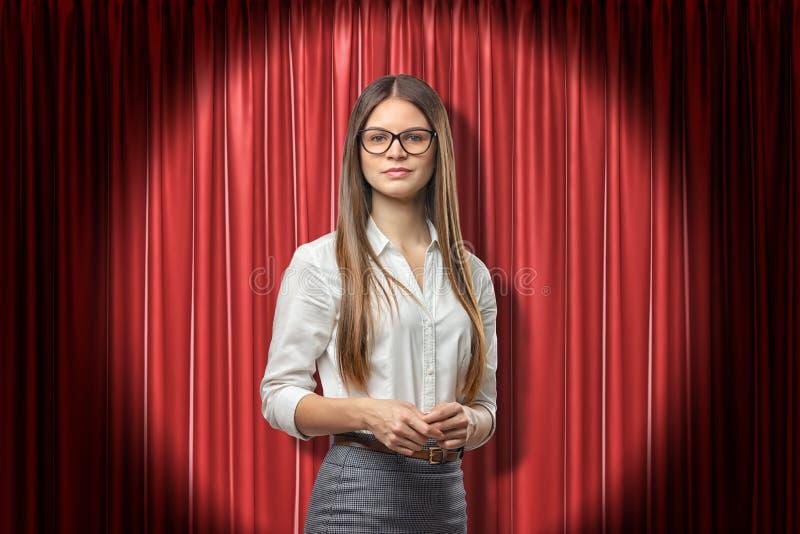 Jonge aantrekkelijke vrouw in wit bureauoverhemd, grijze rok en glazen, die zich in schijnwerper tegen rood stadiumgordijn bevind stock fotografie