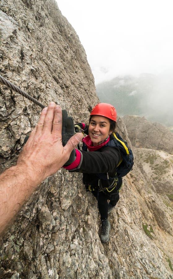Jonge aantrekkelijke vrouwelijke alpinist in het Dolomiet die van Italië een hoogte vijf voor succes geven royalty-vrije stock foto
