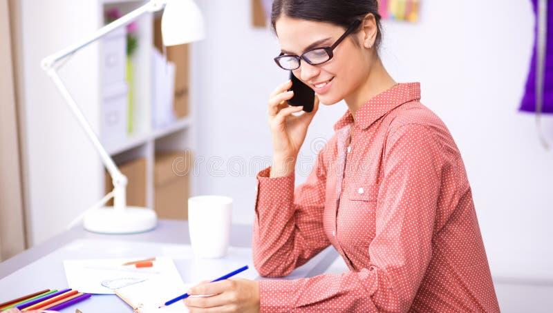 Download Jonge Aantrekkelijke Vrouwelijke Manierontwerper Die Bij Bureau Werkt, Dat Terwijl Het Spreken Op Mobiel Trekt Stock Afbeelding - Afbeelding bestaande uit kaukasisch, handbediend: 107704737