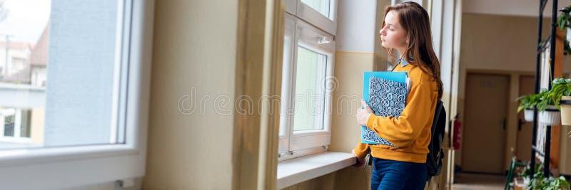 Jonge aantrekkelijke vrouwelijke middelbare schoolstudent die zich door het venster in de gang op haar alleen school bevinden stock foto