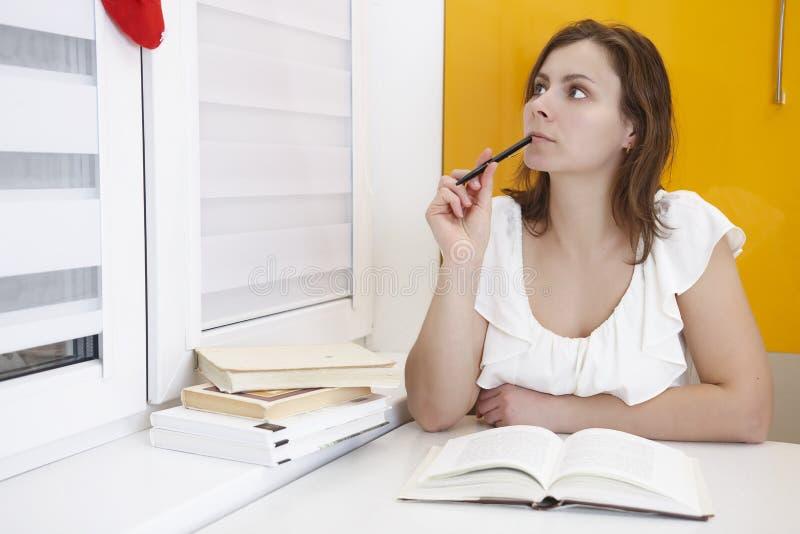 Jonge aantrekkelijke vrouwelijke student die voor examens met handboeken op de lijst voorbereidingen treffen Leer de lessen royalty-vrije stock afbeeldingen