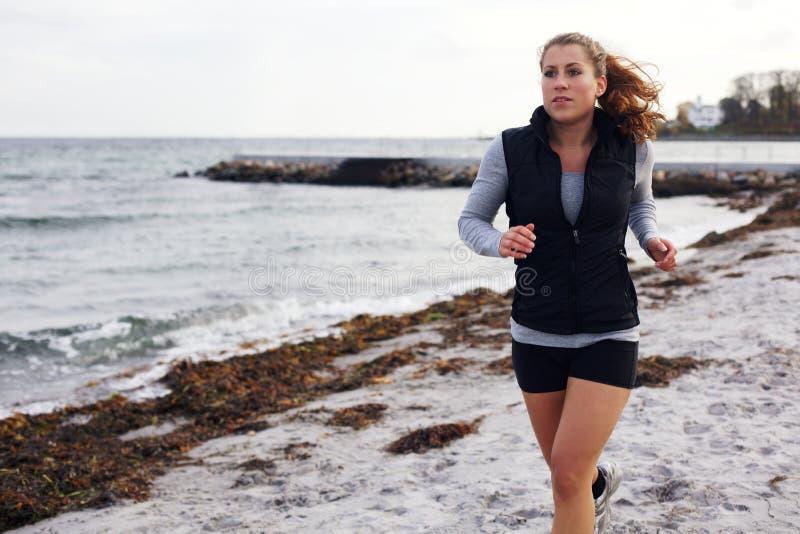 Jonge aantrekkelijke vrouwenjogging op een zandig strand royalty-vrije stock foto's