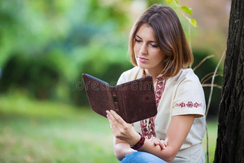 Jonge aantrekkelijke vrouwenlezing eBook in park stock foto
