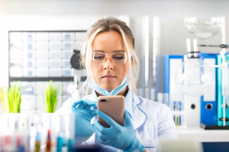 Jonge aantrekkelijke vrouwenwetenschapper die smartphone in laborat gebruiken stock foto