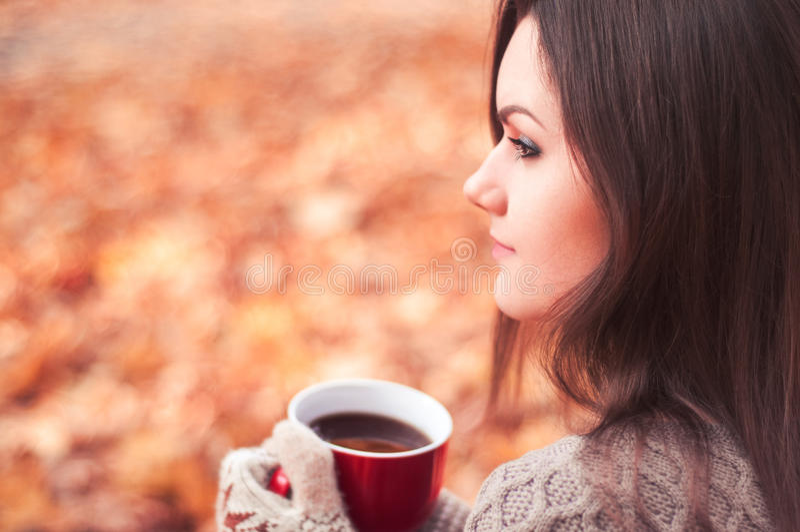 Jonge aantrekkelijke vrouwenzitting in een een park en het drinken thee stock afbeeldingen