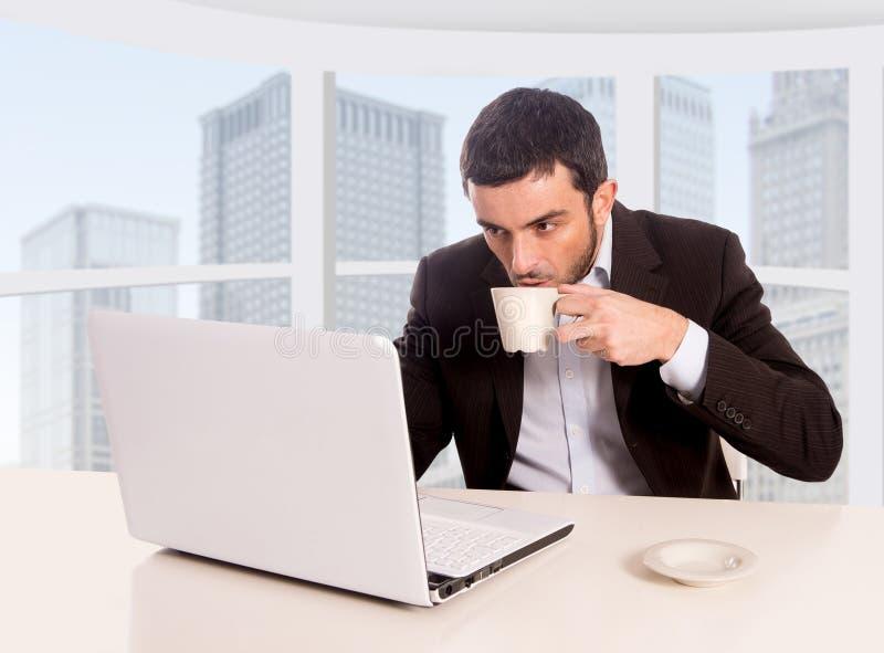 Jonge aantrekkelijke zakenman die bij commerciële districtskantoorzitting bij computerbureau het drinken koffie werken royalty-vrije stock afbeelding