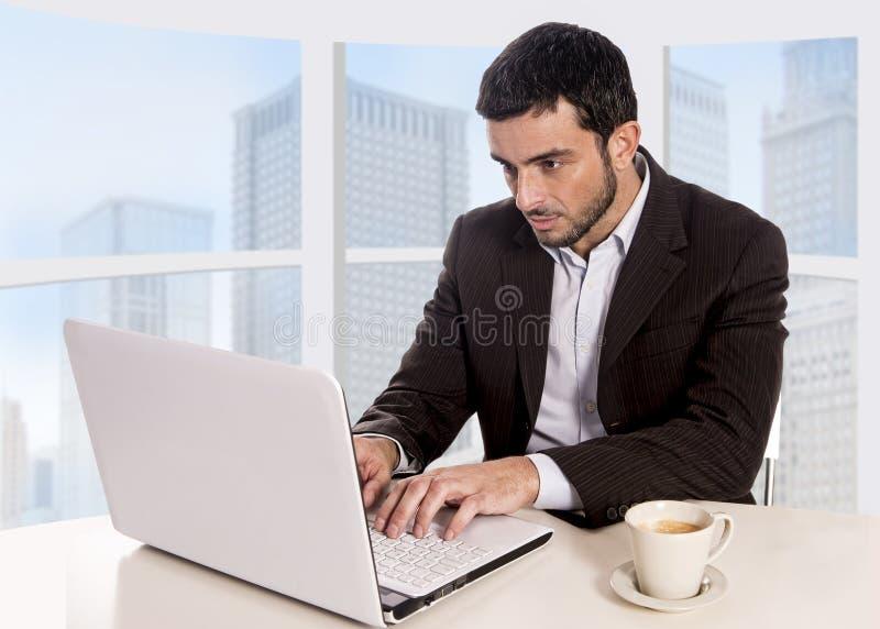 Jonge aantrekkelijke zakenman die bij commerciële districtskantoorzitting bij computerbureau werken met koffiekop stock fotografie