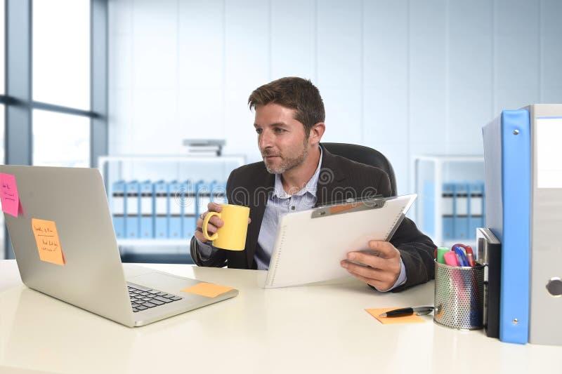 Jonge aantrekkelijke zakenman die gelukkige zeker werken op kantoor met laptop computer en administratie stock afbeeldingen