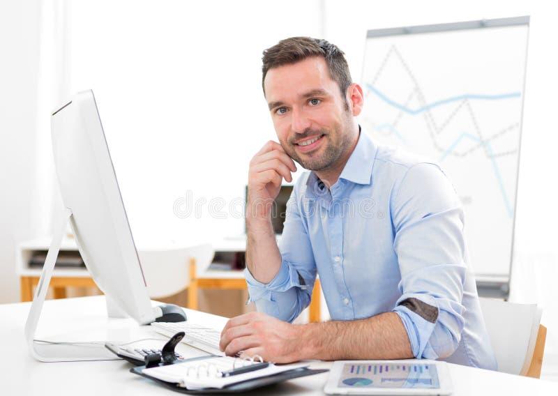 Jonge aantrekkelijke zakenman op het kantoor royalty-vrije stock afbeelding