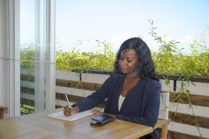 Jonge aantrekkelijke zwarte Afrikaanse Amerikaanse vrouwenzitting in openlucht bij koffiewinkel bezig en gelukkig werken stock foto's