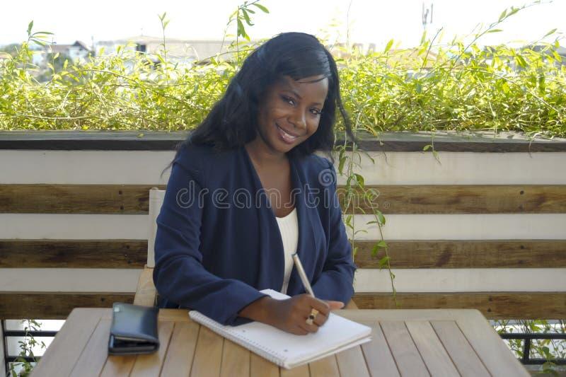 Jonge aantrekkelijke zwarte Afrikaanse Amerikaanse vrouwenzitting in openlucht bij koffiewinkel bezig en gelukkig werken royalty-vrije stock foto's