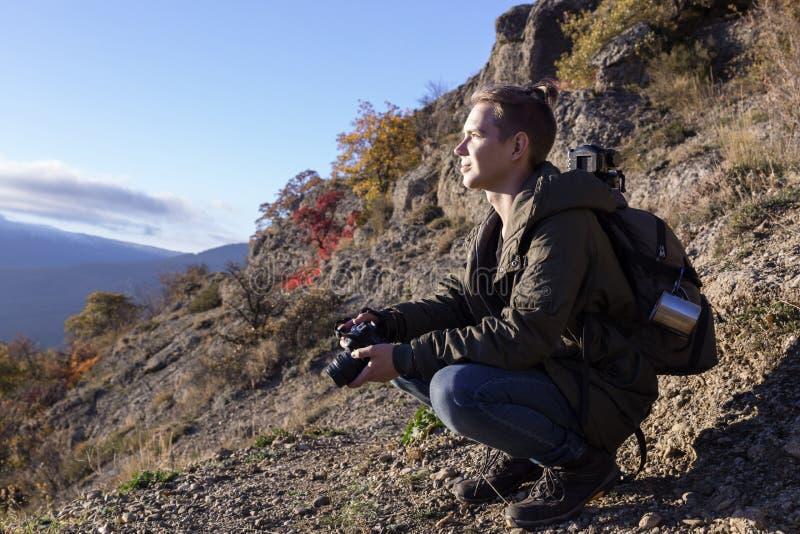 Jonge aardige kerel met rugzak in de bergen die de afstand onderzoeken en een camera houden stock fotografie