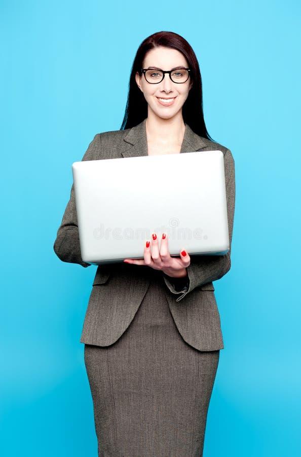 Jonge actieve onderneemster die aan laptop werkt stock foto