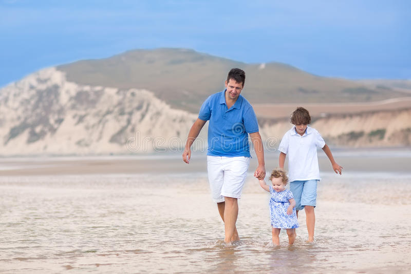 Jonge actieve vader bij mooi strand met zijn jonge geitjes stock foto