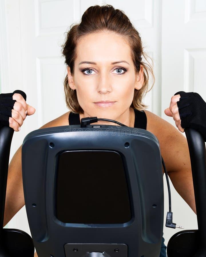 Jonge actieve vrouw die hometrainer voor cardiotraining met behulp van stock foto