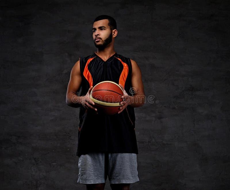 Jonge Afrikaans-Amerikaanse basketbalspeler in sportkleding over donkere achtergrond stock afbeeldingen