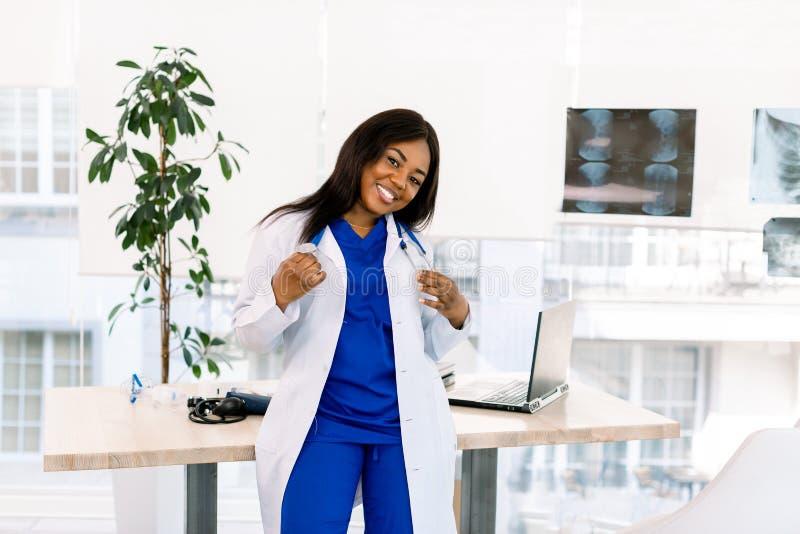 Jonge Afrikaans-Amerikaanse dokter, vrouwtje met lang haar met een medisch uniform, gelukkig Medisch en royalty-vrije stock afbeeldingen