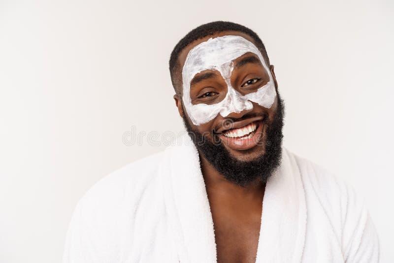 Jonge Afrikaans-Amerikaanse kerel die gezichtsroom op witte achtergrond toepassen Portret van een jonge gelukkige glimlachende Af royalty-vrije stock foto's