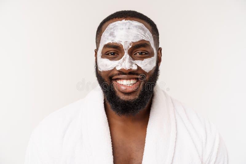 Jonge Afrikaans-Amerikaanse kerel die gezichtsroom op witte achtergrond toepassen Portret van een jonge gelukkige glimlachende Af stock foto