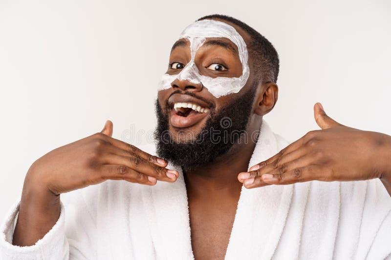 Jonge Afrikaans-Amerikaanse kerel die gezichtsroom op witte achtergrond toepassen Portret van een jonge gelukkige glimlachende Af stock fotografie