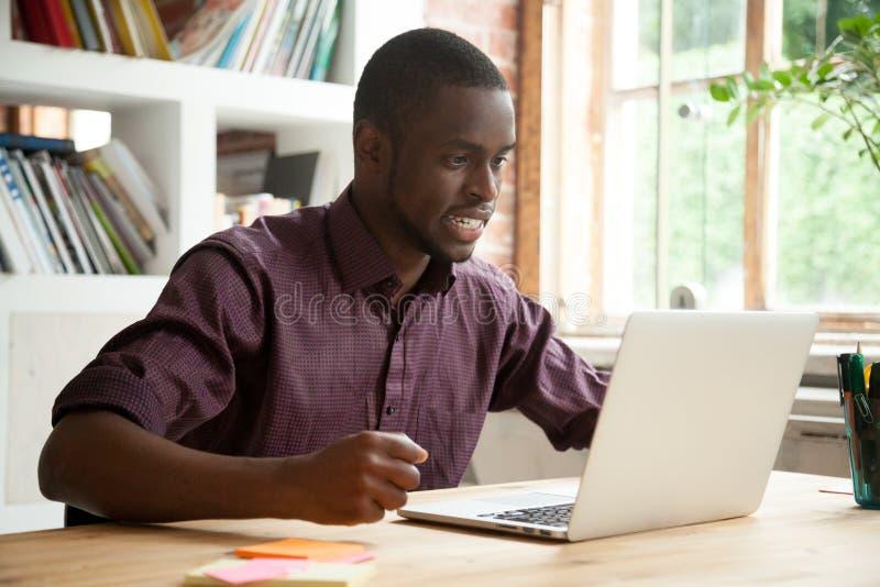 Jonge Afrikaans-Amerikaanse mens die die laptop bekijken door slecht n wordt gefrustreerd stock foto's