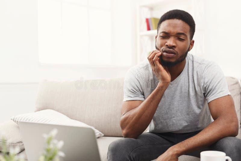 Jonge Afrikaans-Amerikaanse mens die tandpijn hebben thuis stock afbeeldingen