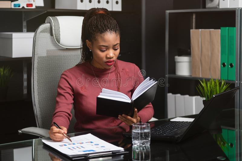 Jonge Afrikaans-Amerikaanse onderneemster die met documenten en notitieboekje bij computerbureau werken in bureau stock afbeelding