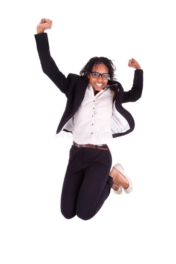 Jonge Afrikaanse Amerikaanse bedrijfsvrouw die, succesconcept springen royalty-vrije stock foto