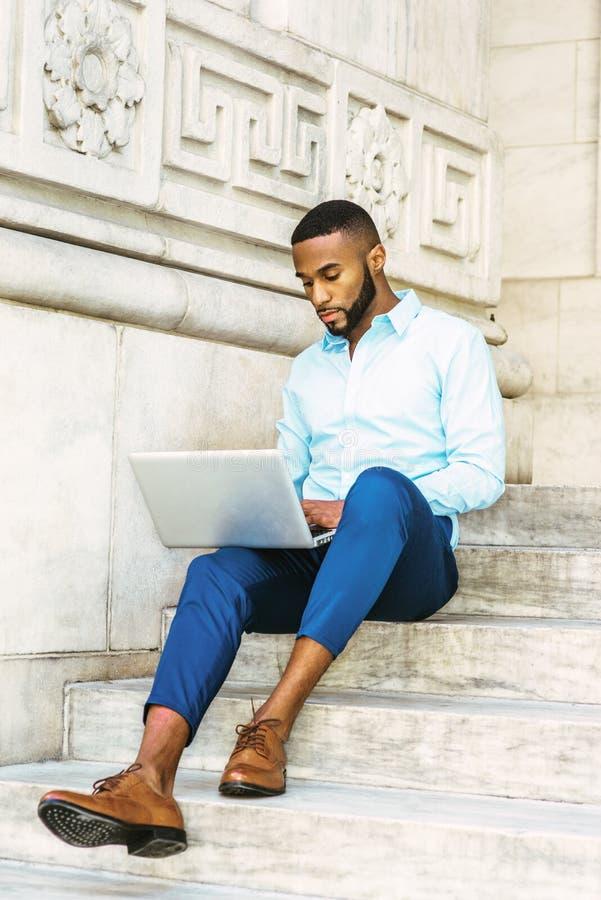 Jonge Afrikaanse Amerikaanse gediplomeerde student die met baard in N bestuderen stock afbeelding