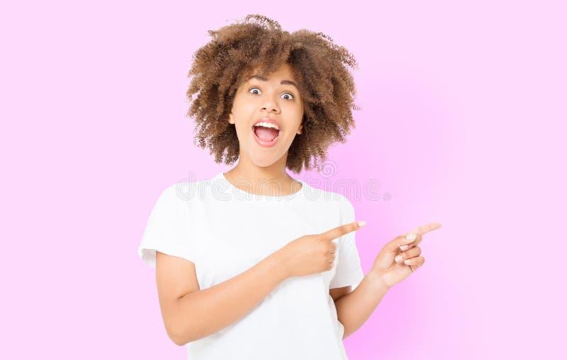 Jonge Afrikaanse Amerikaanse gelukkige vrouw die copyspace het richten op geïsoleerde roze achtergrond tonen Jongen en de meisjes stock fotografie